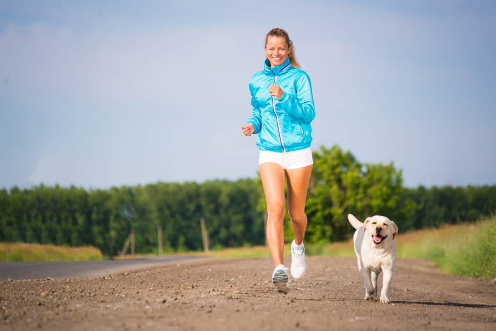 A Girl is Running With a Dog