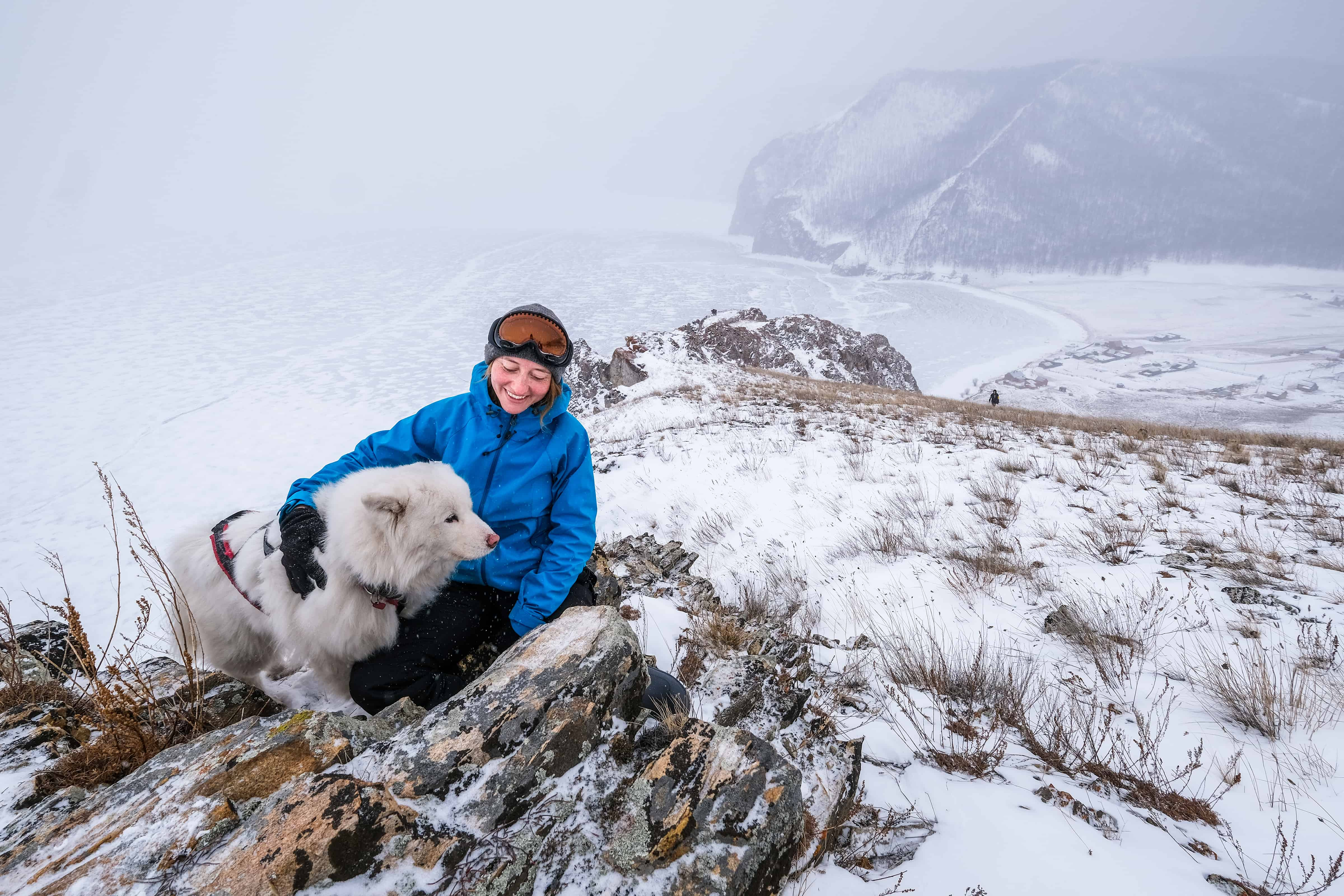 A Woman is Winter Hiking with Her Dog